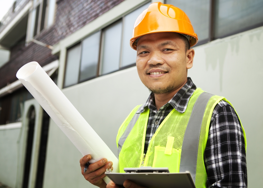 Male construction worker wearing safety vest at a building site